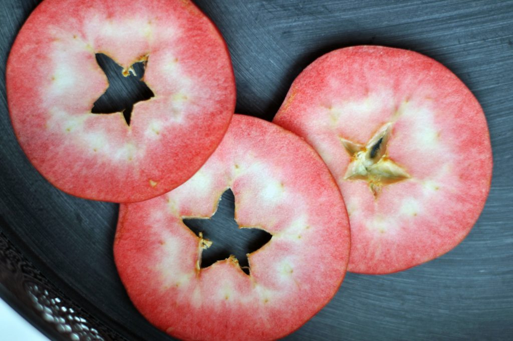 Three Slices of Red Love Apples on a dark background